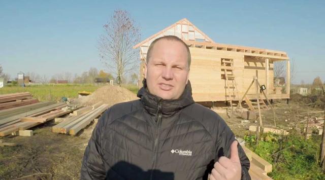 на фото Роман с большим пальцем вверх на фоне одноэтажного каркасного дома